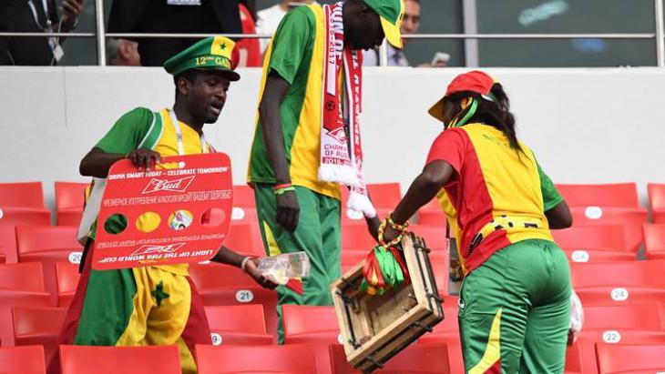 Сенегальцы убирают за собой мусор на стадионе